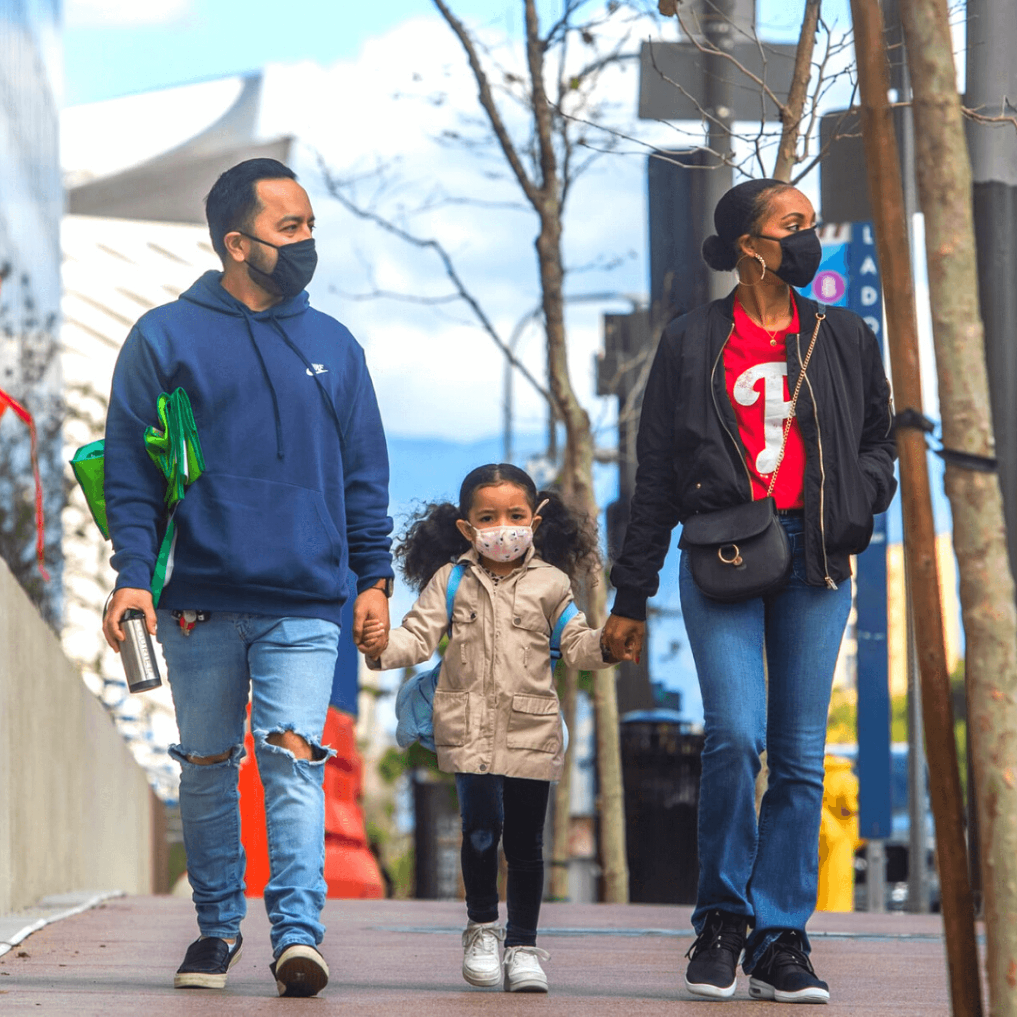 Family walking down street, parents and child wearing face masks and holding hands.